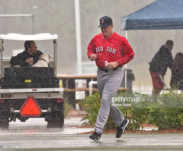 Boston Red Sox manager John Farrell runs for cover after leaving the covered batting cage back to their clubhouse Day three of spring training at the...