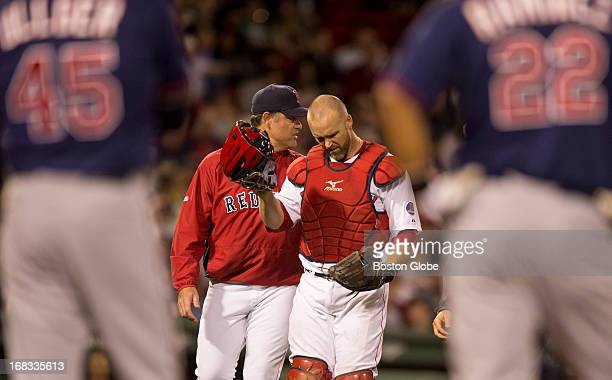 Boston Red Sox manager John Farrell walks off the field with David Ross after Ross was injured trying to catch a foul ball hit by Minnesota Twins...