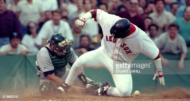 Boston Red Sox Mo Vaughn slides safely into home plate against Oakland Athletic catcher Terry Steinbach who bobbled the throw from left field on a...
