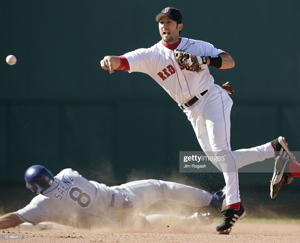 Boston Red Sox Nomar Garciaparra, right, turn a double play as Los Angeles Dodgers' base runner Olmedo Saenz slides into second at Fenway Park in Boston, Massachusetts on June 12, 2004.