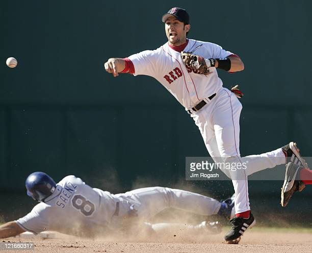 Boston Red Sox Nomar Garciaparra right turn a double play as Los Angeles Dodgers' base runner Olmedo Saenz slides into second at Fenway Park in...