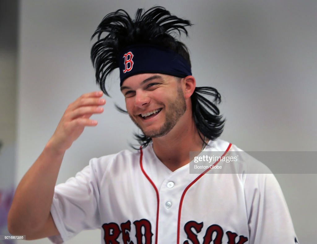 Boston Red Sox outfielder Andrew Benintendi wears a prop hairpiece making light of his hairstyle from the previous season as players posed for promotional photos during spring training at the Player Development Complex at Jet Blue Park in Fort Myers, FL on Feb. 20, 2018.
