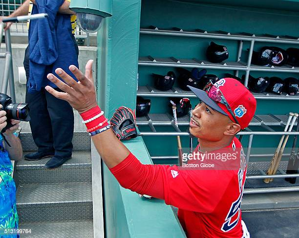 Boston Red Sox outfielder Mookie Betts catches a pen tossed to him by a fan to sign a pregame autograph before a spring training exhibition game...