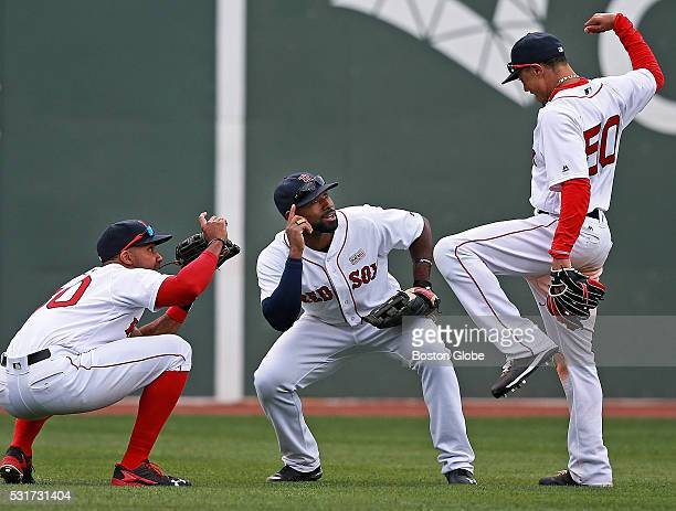Boston Red Sox outfielders Chris Young left and Jackie Bradley Jr get in position to pretend to capture the pose of teammate Mookie Betts right...