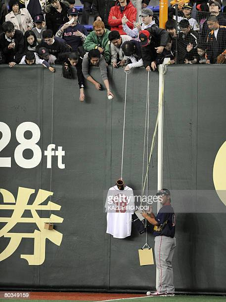 Boston Red Sox pitcher Daisuke Matsuzaka of Japan signs his autograph for Japanese fans before an exhibition game between Red Sox and Japan's Hanshin...