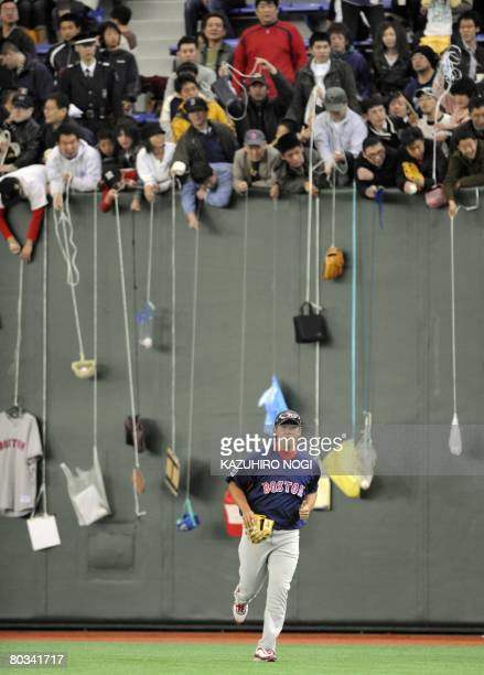 Boston Red Sox pitcher Daisuke Matsuzaka of Japan warms up in front of fans who were dangling items hoping for an autograph before an exhibition game...