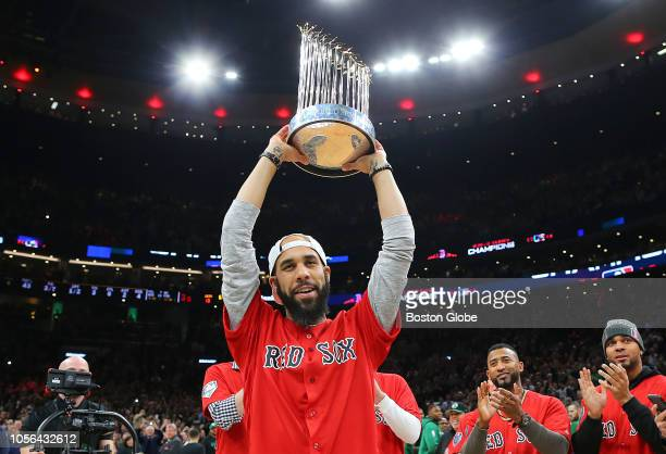 Boston Red Sox pitcher David Price holds the World Series trophy over his head as members of the team are introduced during a timeout of the game to...