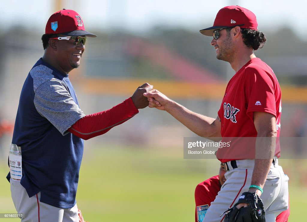 Boston Red Sox pitcher Joe Kelly, right, bumps fists with former Red Sox pitcher Pedro Martinez, left, after he made a play during a spring training drill at the Player Development Complex at Jet Blue Park in Fort Myers, FL on Feb. 17, 2018.