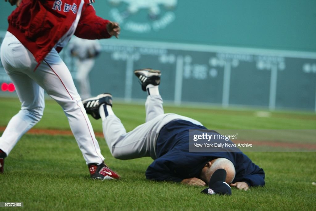 Boston Red Sox' pitcher Pedro Martinez (left) throws 72-year-old New York Yankees' bench coach Don Zimmer to the ground in a fourth-inning fracas at Fenway Park during Game 3 of the American League Championship Series. Martinez had hit the Yankees' Karim Garcia with a pitch at the top of the inning; when Yanks' pitcher Roger Clemens then nearly grazed the Sox' Manny Ramirez, a bench-clearing brawl ensued. Zimmer, who lunged at Martinez during the dustup, was taken to the hospital for observation, then released. The Yanks won, 4-3.