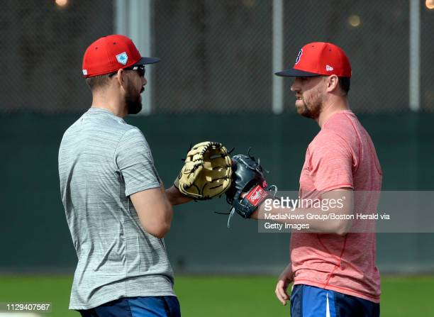 Boston Red Sox pitchers Matt Barnes and Heath Hembree bump gloves after throwing during a spring training workout in Fort Myers Florida on February...