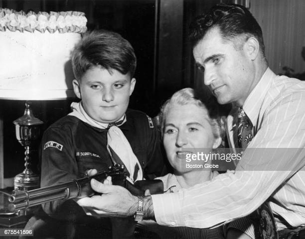 Boston Red Sox player Bobby Doerr holds a rifle with his son Donnie in a Boy Scout uniform left and his wife Monica on their last day in Boston Sep...