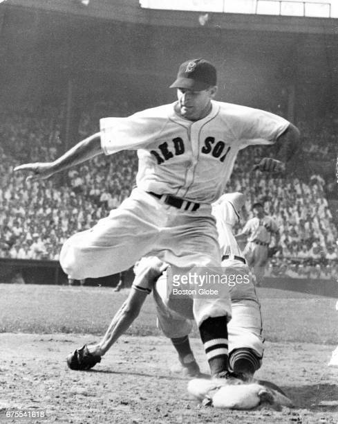 Boston Red Sox player Bobby Doerr is out on a throw from Cleveland Indians' Lou Boudreau to Eddie Robinson during a game at Fenway Park in Boston on...