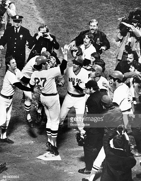 Boston Red Sox player Carlton Fisk center receives a hero's welcome at home plate for his winning home run in the sixth game of the World Series...