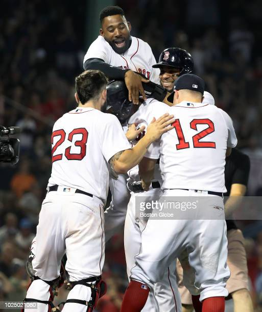 Boston Red Sox player Eduardo Nunez is mobbed by teammates including a leaping Jackie Bradley Jr after he hustled across first base as a throwing...