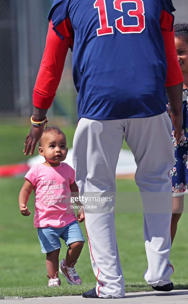 Boston Red Sox player Hanley Ramirez reaches to pick up Emerson, the young daughter of teammate Jackie Bradley, Jr. (not pictured) after the workout on the final day of workouts during spring training at the Player Development Complex at Jet Blue Park in Fort Myers, FL on Feb. 21, 2018. The team begins exhibition games with a doubleheader against college teams the following day.