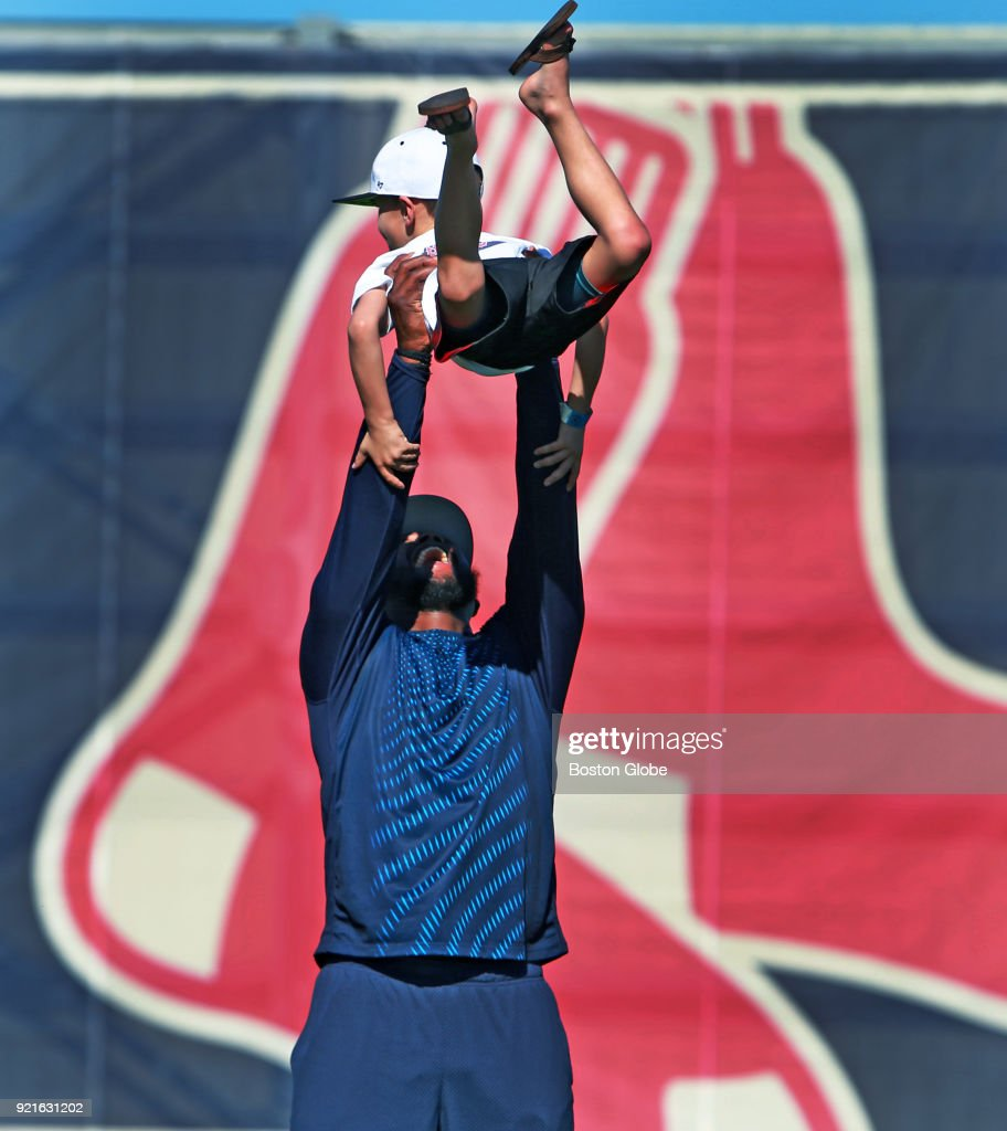 Boston Red Sox player Hanley Ramirez smiles as he hoists Cole Pedroia, the son of his teammate Dustin Pedroia, as Cole and his brothers were playing some ball with their dad during spring training at the Player Development Complex at Jet Blue Park in Fort Myers, FL on Feb. 18, 2018.