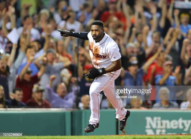 Boston Red Sox player Jackie Bradley Jr celebrates after sliding safely into home in the fourth inning on a hit by teammate Andrew Benintendi The...