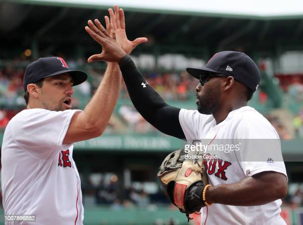 Boston Red Sox player Jackie Bradley Jr gets a high five from starting pitcher Nathan Eovaldi after Bradley robbed Minnesota Twins' Bobby Wilson of...