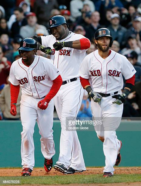 Boston Red Sox player Jackie Bradley Jr left heads back to the dugout as Red Sox teammate David Ortiz center celebrates his three run home run...