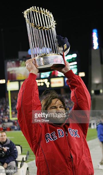 Boston Red Sox player Johnny Damon show off the World Series trophy before the New England Patriots game against the Buffalo Bills at Gillette...