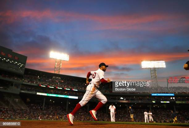 Boston Red Sox player Mookie Betts runs to the outfield at the end of the third inning under a colorful sunset The Boston Red Sox host the Baltimore...