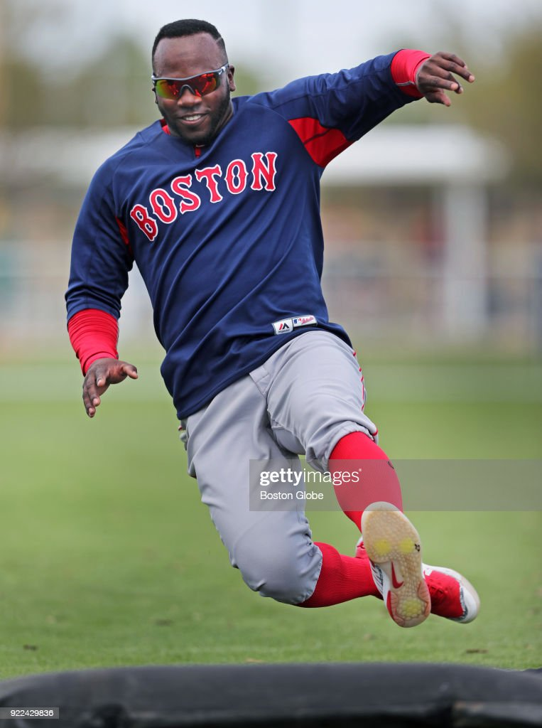 Boston Red Sox player Rusney Castillo is airborne as he takes part in a sliding drill on the final day of workouts during spring training at the Player Development Complex at Jet Blue Park in Fort Myers, FL on Feb. 21, 2018. The team begins exhibition games with a doubleheader against college teams the following day.