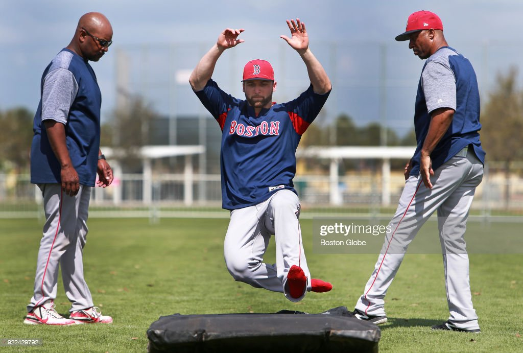 Boston Red Sox player Sam Travis takes part in a base sliding drill on the final day of workouts during spring training at the Player Development Complex at Jet Blue Park in Fort Myers, FL on Feb. 21, 2018. The team begins exhibition games with a doubleheader against college teams the following day.