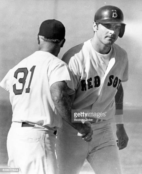 Boston Red Sox player Tony Conigliaro is congratulated by first base coach Bobby Doerr after Conigilaro drove in the winning run in the ninth inning...