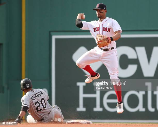 Boston Red Sox player Xander Bogaerts turns a double play forcing out Chicago White Sox player Jose Rondon during the sixth inning The Boston Red Sox...