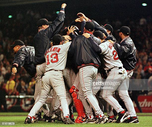 Boston Red Sox players mob winning pitcher Pedro Martinez at the mound after winning game five of the American League Division Series playoff against...