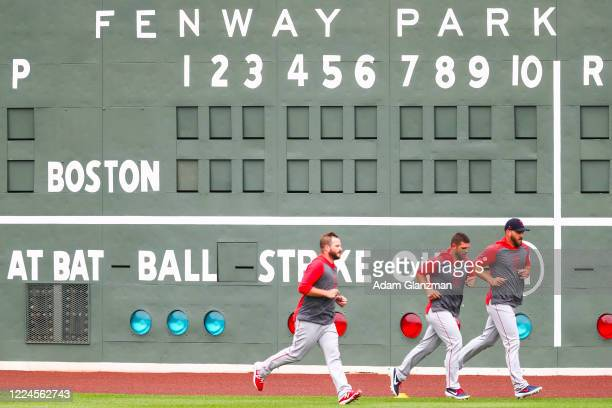 Boston Red Sox players run by the Green Monster scoreboard during Summer Workouts at Fenway Park on July 3, 2020 in Boston, Massachusetts.