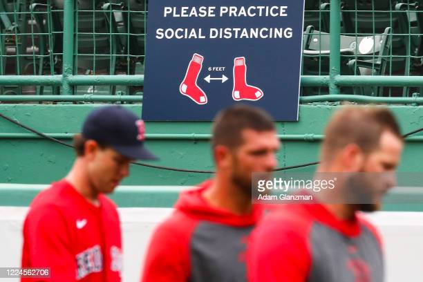 Boston Red Sox players walk by a sign encouraging social distancing during Summer Workouts at Fenway Park on July 3, 2020 in Boston, Massachusetts.