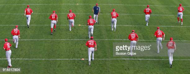 Boston Red Sox players warm up before the start of a workout on the first official day of spring training for pitchers and catchers at the Player...