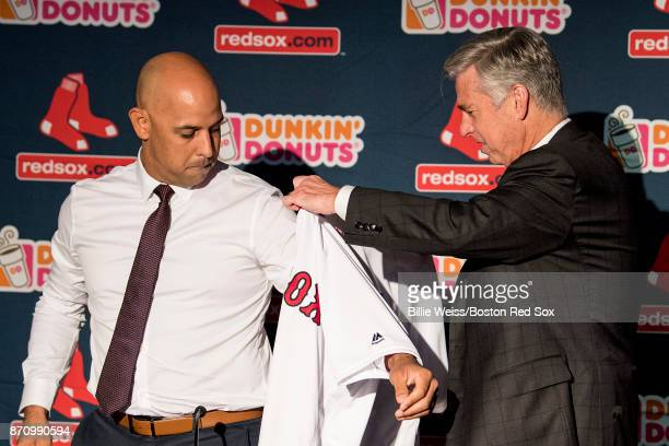 Boston Red Sox President of Baseball Operations Dave Dombrowski presents Alex Cora with a jersey during a press conference introducing him as the...