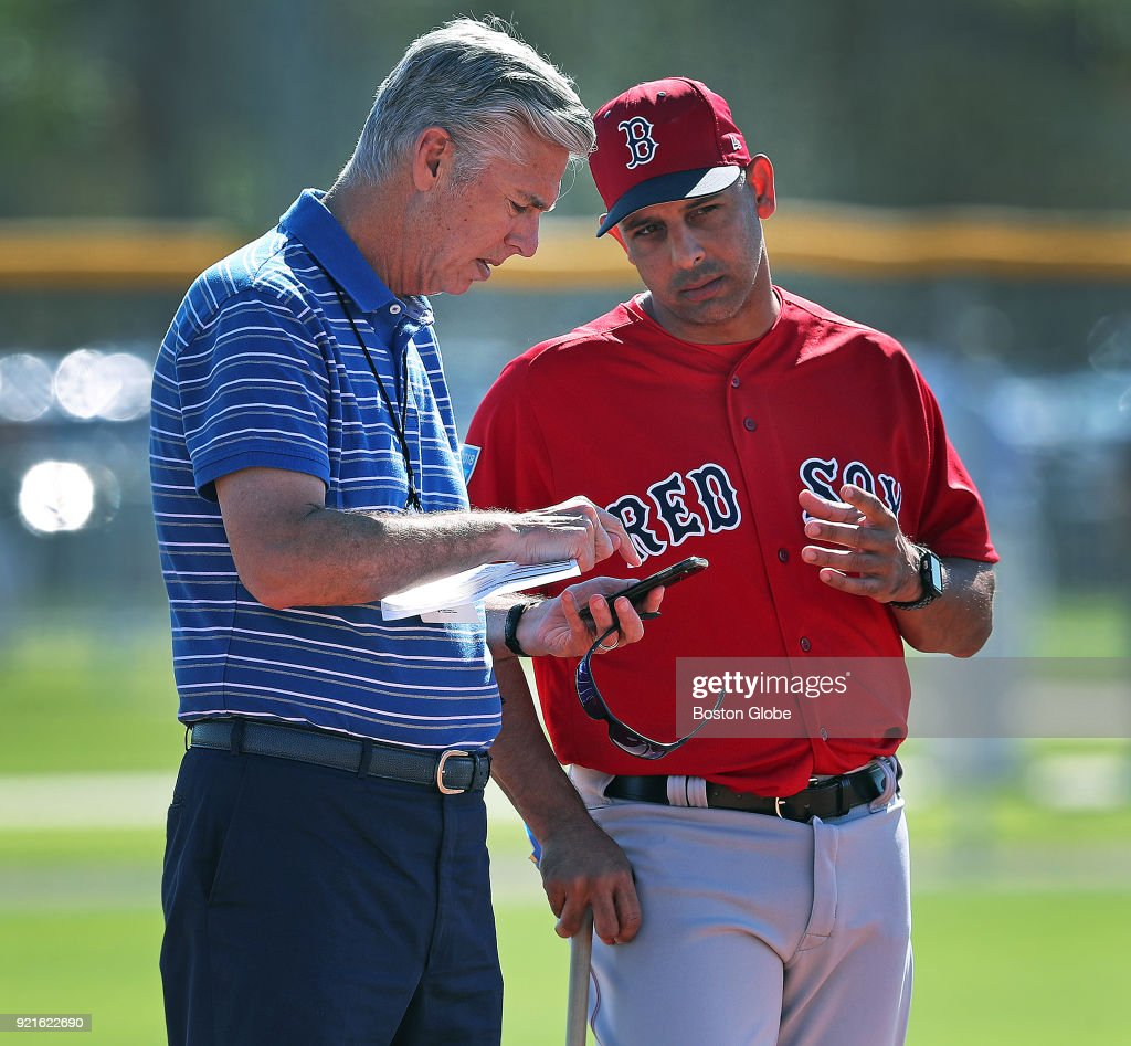 Boston Red Sox president of baseball operations Dave Dombrowski, left, dials a phone call while talking to manager Alex Cora in the infield as pitchers do drills on the mound during spring training at the Player Development Complex at Jet Blue Park in Fort Myers, FL on Feb. 17, 2018.