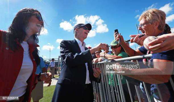 Boston Red Sox principal owner John Henry and his wife Linda Pizzuti Henry left share a laugh with a fan as Henry signs some autographs on the day of...