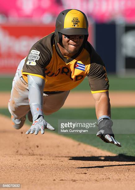 Boston Red Sox prospect Yoan Moncada of the World Team slides headfirst into third base during the SiriusXM AllStar Futures Game at PETCO Park on...