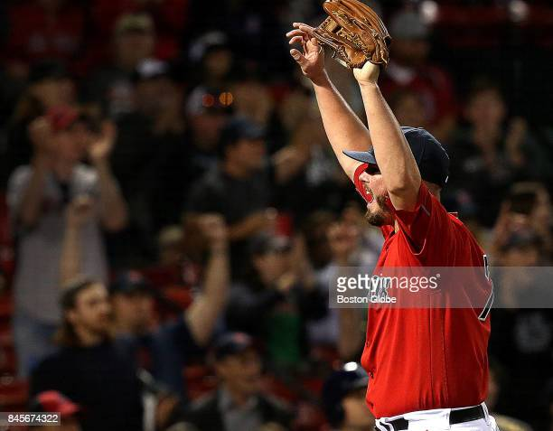 Boston Red Sox relief pitcher Austin Maddox celebrates a leaping catch by Boston Red Sox center fielder Jackie Bradley Jr up against the center field...