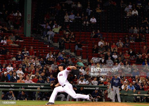 Boston Red Sox relief pitcher Craig Breslow pitches during the ninth inning to empty seats and a disgruntled fan with a sign as the Boston Red Sox...