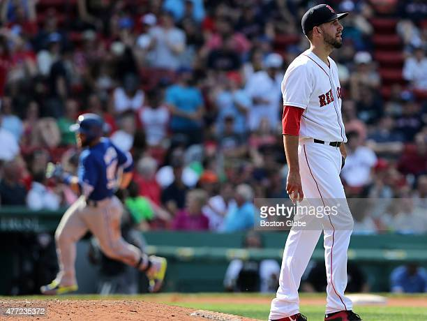 Boston Red Sox relief pitcher Matt Barnes looks towards center field where Toronto Blue Jays catcher Russell Martin at left circling the bases...