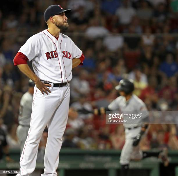 Boston Red Sox relief pitcher Matt Barnes stands as the Marlins' Starlin Castro rounds third base in the background at right following his top of the...