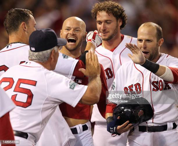 Boston Red Sox right fielder Cody Ross celebrates with his teammates and Boston Red Sox manager Bobby Valentine after hitting a game winning three...