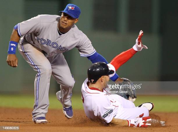 Boston Red Sox right fielder Cody Ross slides safely into second base on a wild pitch by Toronto Blue Jays relief pitcher Carlos Villanueva , not...