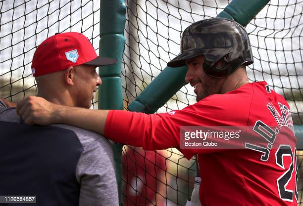Boston Red Sox right fielder JD Martinez and Boston Red Sox manager Alex Cora share a light moment during live batting practice during spring...
