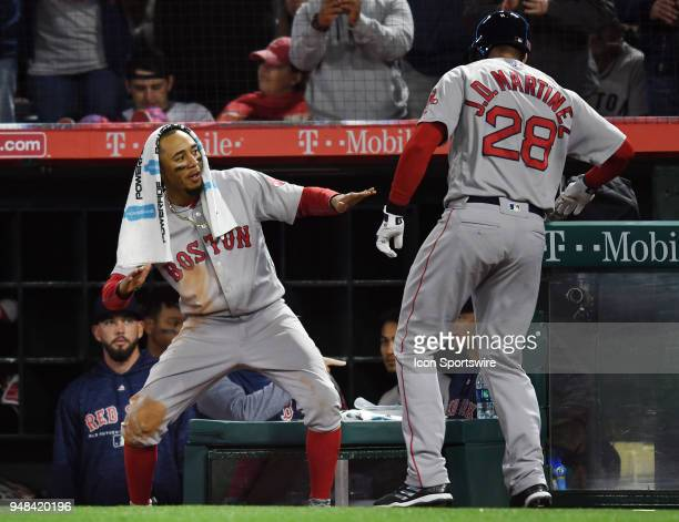 Boston Red Sox right fielder Mookie Betts greets left fielder JD Martinez after Martinez hit a solo home run in the ninth inning of a game against...