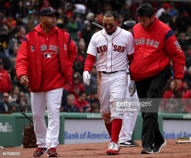 Boston Red Sox right fielder Mookie Betts is assisted off the field after he was shaken up sliding home during the first inning Betts left the game...