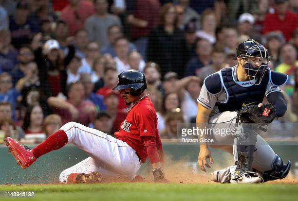 Boston Red Sox right fielder Mookie Betts scores on a sacrifice fly ball hit by Boston Red Sox shortstop Xander Bogaerts in the fifth inning. The...