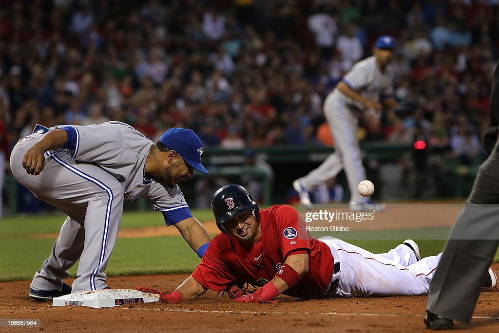 Boston Red Sox right fielder Shane Victorino (#18) dives back to first but the pick off throw got away from Toronto Blue Jays first baseman Edwin Encarnacion (#10), allowing Victorino to take second base during the third inning. The Boston Red Sox take on the Toronto Blue Jays at Fenway Park.