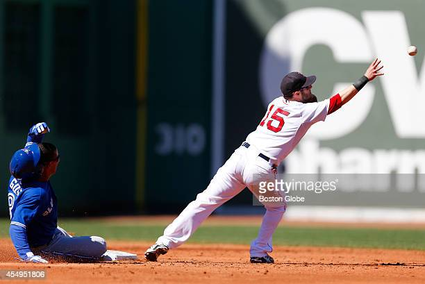 Boston Red Sox second baseman Dustin Pedroia reaches for the ball too late to tag out Toronto Blue Jays Anthony Gose left during the third inning of...