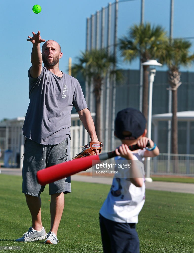 Boston Red Sox second baseman Dustin Pedroia, rehabbing from major restoration cartilage surgery on his left knee, pitches to his youngest son Brooks as they have some fun during spring training at the Player Development Complex at Jet Blue Park in Fort Myers, FL on Feb. 18, 2018.